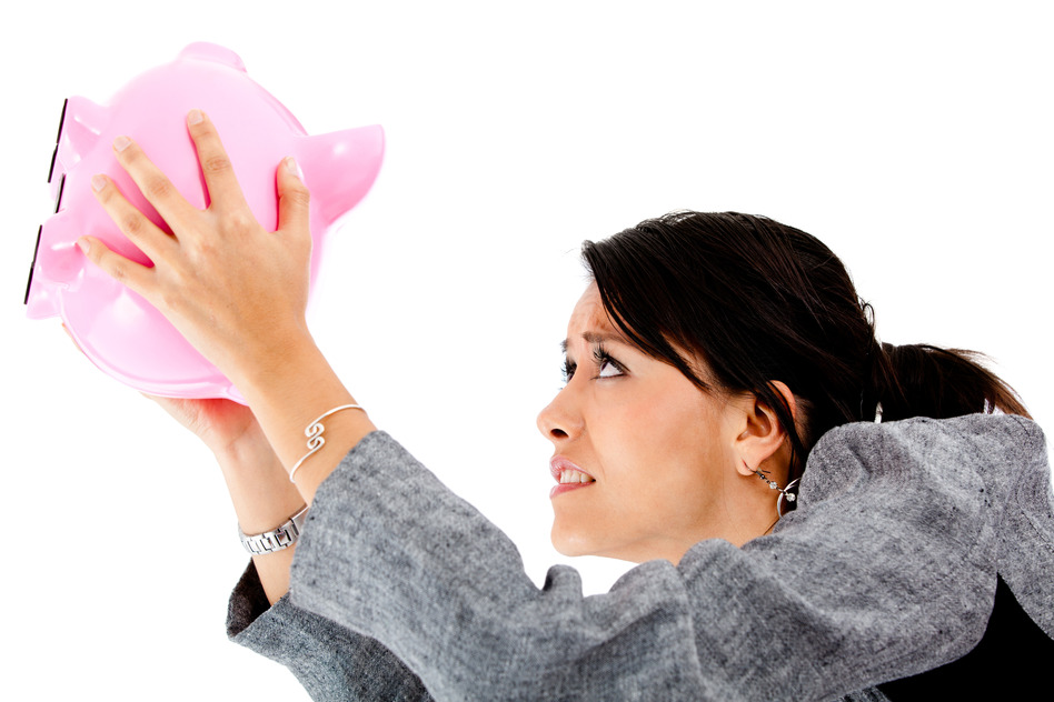 Woman trying to take money out of a piggybank