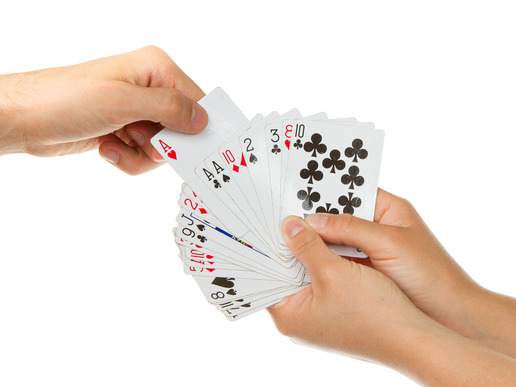 Man picking a playing card from a deck of cards